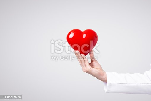 1035479448 istock photo Male doctor holding heart in his arms. Healthcare and cardiology concept in medicine 1142275976