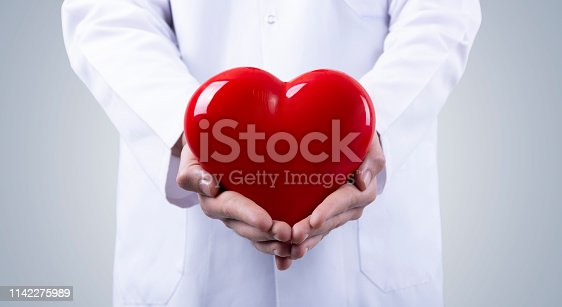 1035479448 istock photo Male doctor holding heart in his arms. Healthcare and cardiology concept in medicine 1142275989