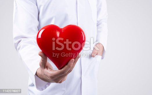 1035479448 istock photo Male doctor holding heart in his arms. Healthcare and cardiology concept in medicine 1142276027