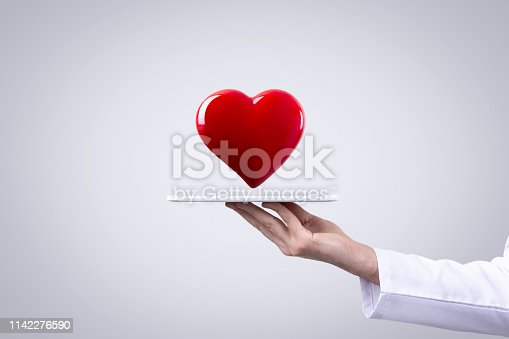 Male doctor holding heart in his arms. Healthcare and cardiology concept in medicine