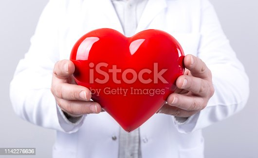 1035479448 istock photo Male doctor holding heart in his arms. Healthcare and cardiology concept in medicine 1142276636
