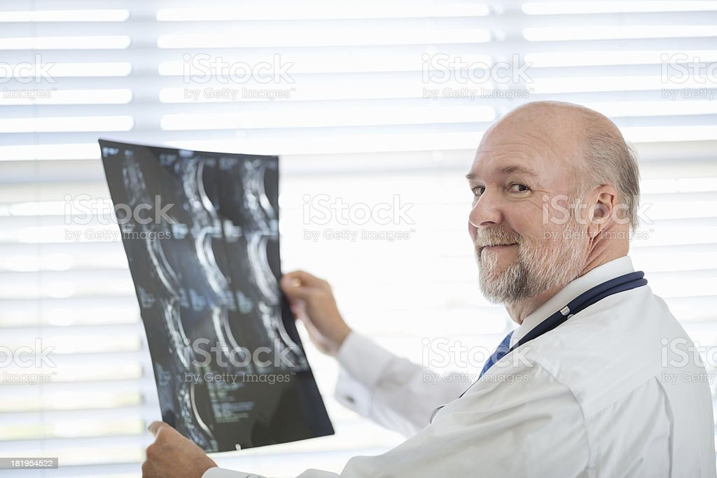 Male Doctor Holding X-ray Report In Clinic royalty-free stock photo