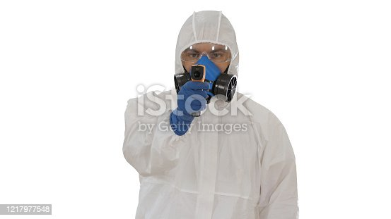 Medium shot. Male doctor in protective suit holding an digital infrared thermometer pointing with it to camera on white background. Professional shot