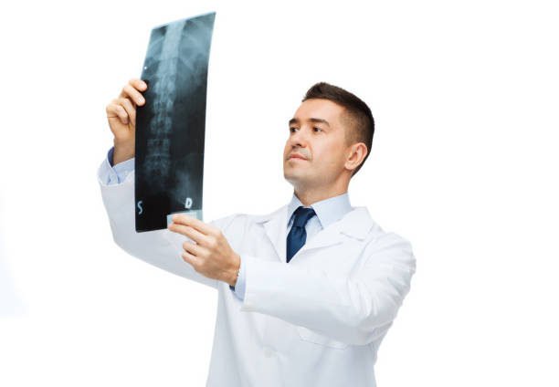 male doctor in white coat looking at x-ray stock photo