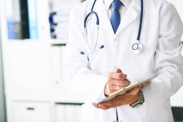Männlicher Arzt im weißen Mantel im Dienst schreibt Informationen mit Stift in Zwischenablage aus nächster Nähe. Selektiver Fokus. Gesundheits- und medizinisches Konzept. – Foto