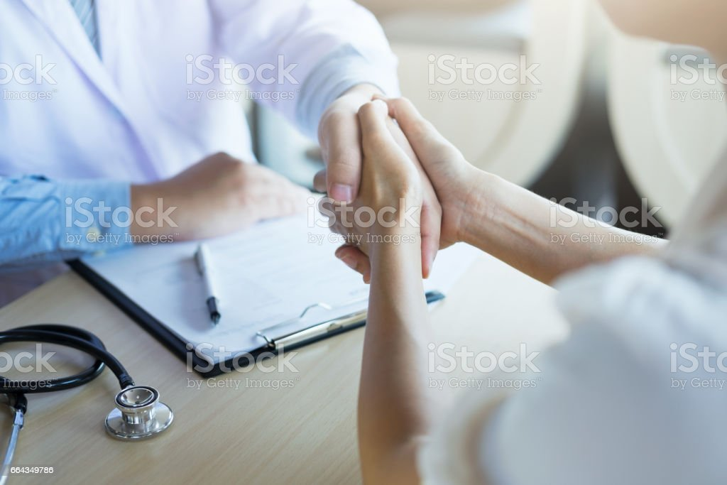 Male doctor in white coat shaking hand to female colleague – Foto