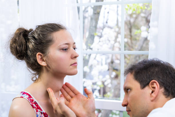Male doctor inspecting, doing palpation examination of young woman with Grave's disease hyperthyroidism symptoms of enlarged thyroid gland goiter and ophthalmopathy in hospital stock photo