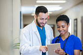istock Male doctor looking at digital tablet and discussing medical results with nurse 1201050293