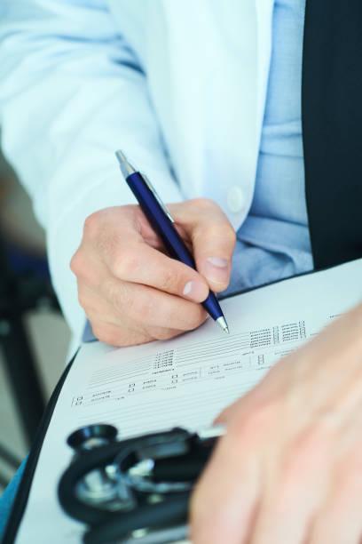 Männlicher Arzt im weißen Mantel mit Stift in der Hand Füllung Rezept oder Checkliste Dokument aus der Nähe. Selektive Fokussierung auf Stift, Gesundheit und Medizinkonzept. – Foto