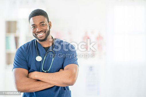 A man in a doctor's coat is standing and smiling at the camera with his arms crossed. He is in a medical clinic.