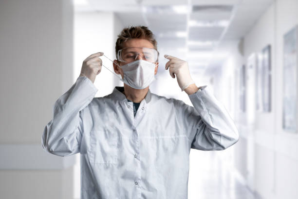 male doctor put on protective uniform with mask and eye glasses in the hospital stock photo
