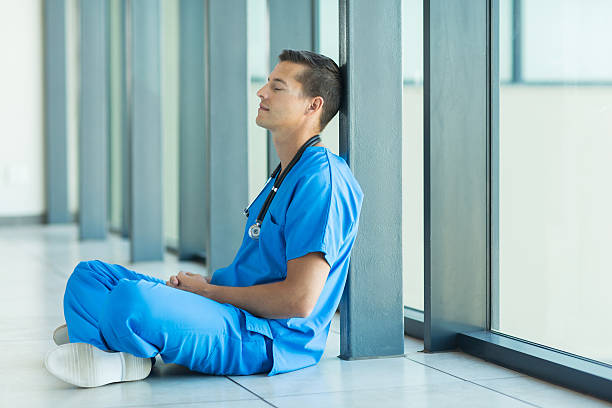 male doctor relaxing on hospital floor stock photo