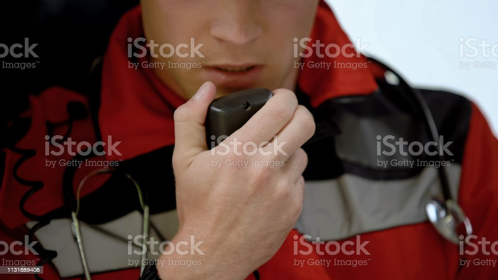 Male doctor responds by radio in ambulance, urgent call to car accident, closeup stock photo