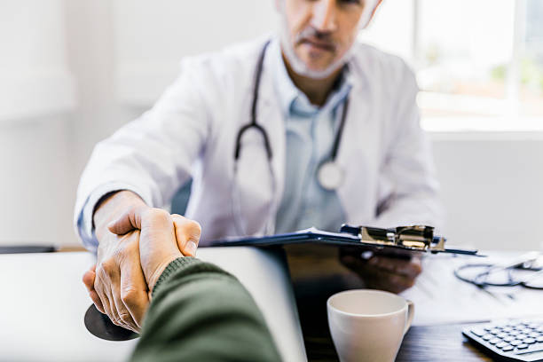 Male doctor shaking hands with patient in clinic stock photo