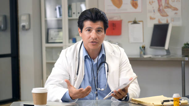 Male doctor shares advice during web conference stock photo