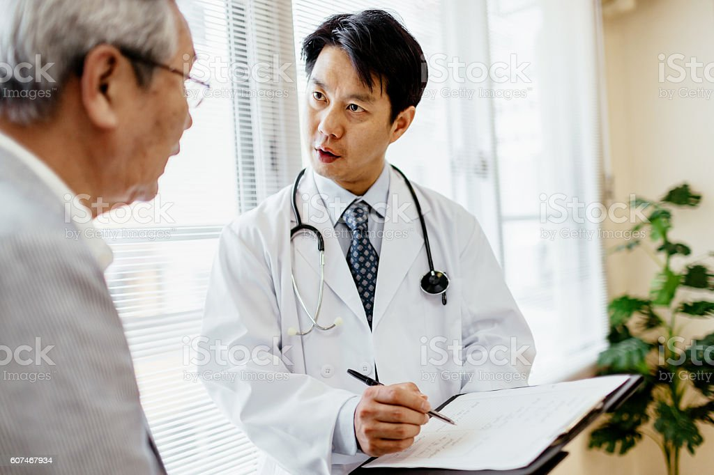 Male doctor showing record to senior patient圖像檔