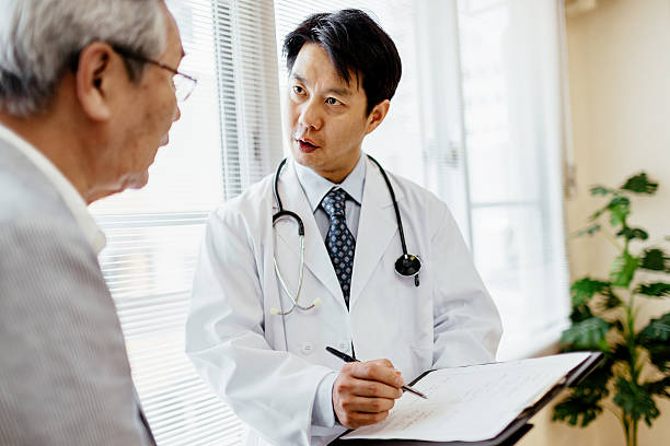 Male doctor showing record to senior patient stock photo