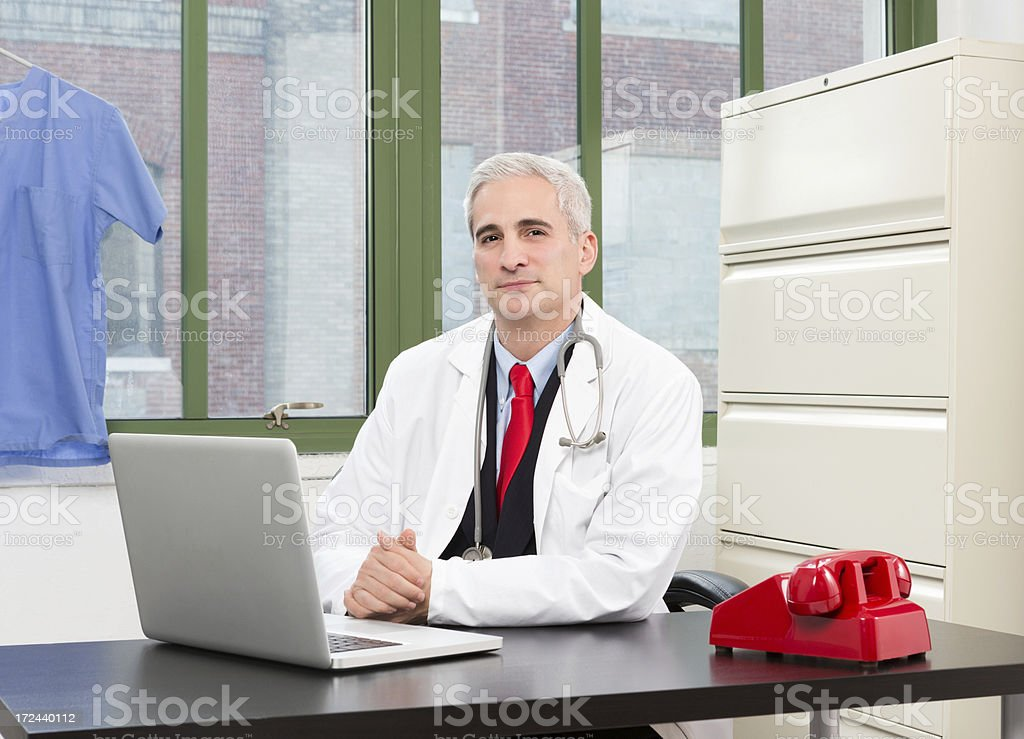Male Doctor Sitting In Front Of Laptop royalty-free stock photo