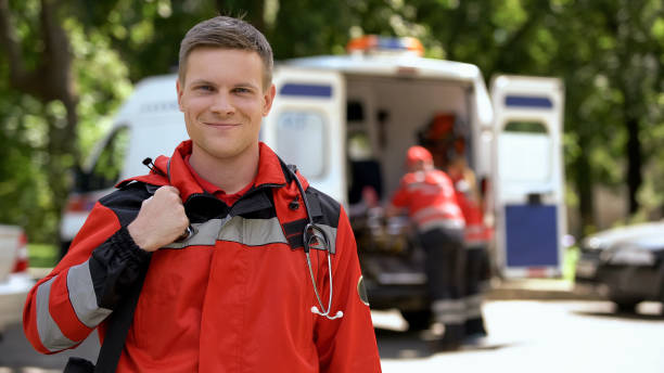 Male doctor smiling into camera, ambulance crew working, blurred on background Male doctor smiling into camera, ambulance crew working, blurred on background ambulance staff stock pictures, royalty-free photos & images