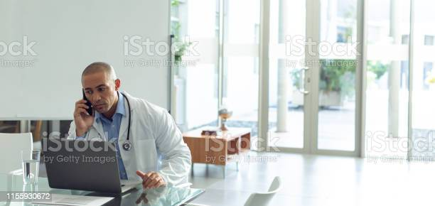 Male doctor talking on mobile phone while using laptop at table in picture id1155930672?b=1&k=6&m=1155930672&s=612x612&h=fsj kbawwfxrlprnroznbybqc1muuinkbnk9muz89qq=