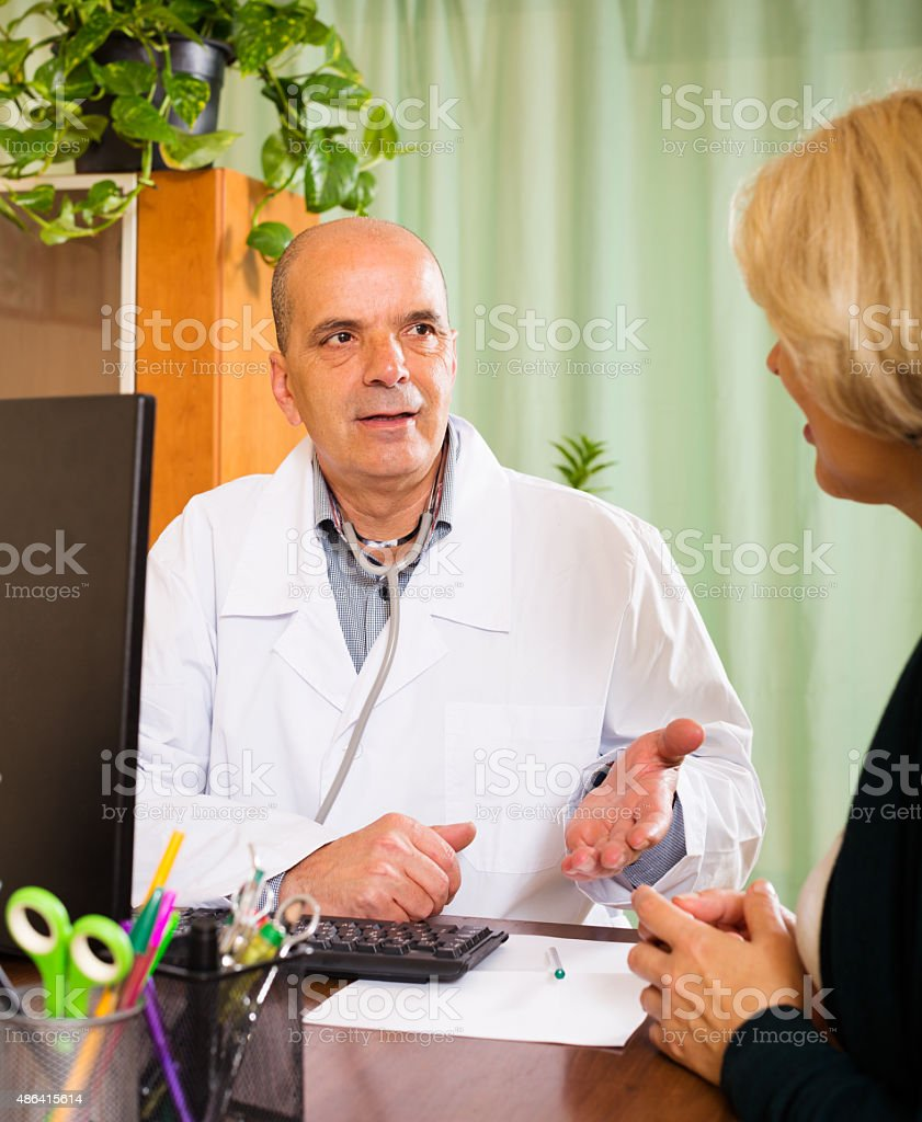 Male doctor talking with mature patient stock photo