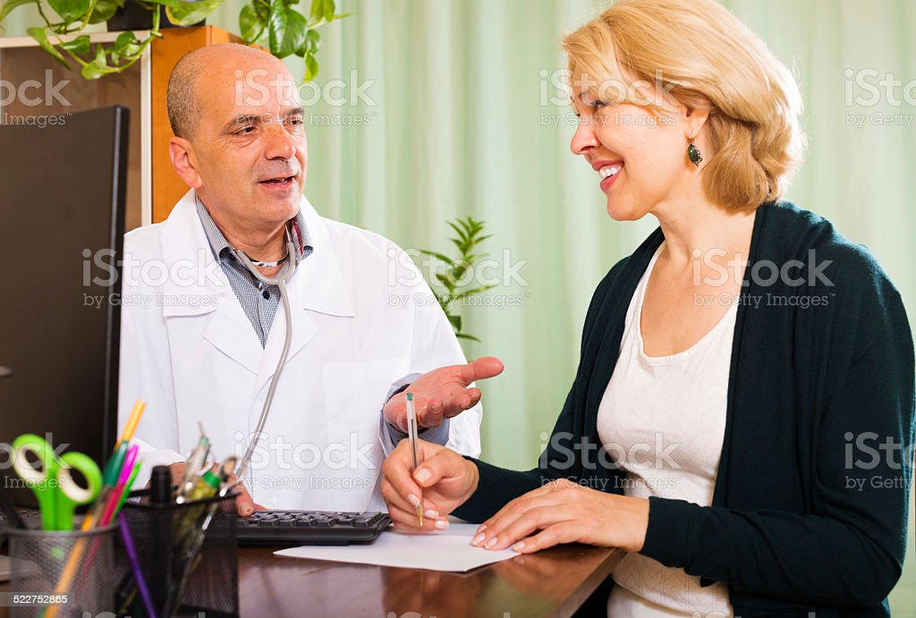 Male doctor talking with smiling mature patient stock photo