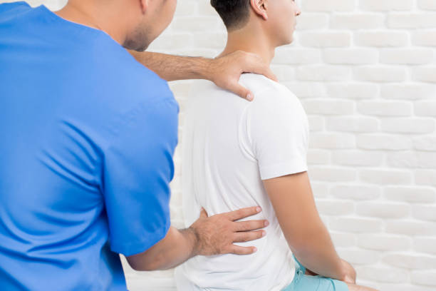 male doctor therapist treating lower back pain patient in clinic or hospital - osteopathy stock pictures, royalty-free photos & images