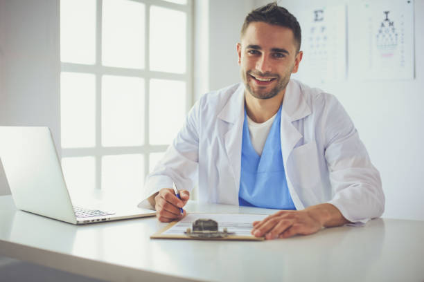 Male doctor using a laptop, sitting at his desk Male doctor using a laptop, sitting at his desk. male animal stock pictures, royalty-free photos & images
