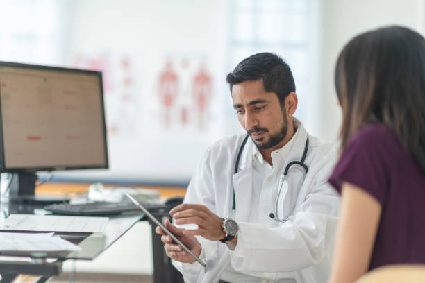 Male doctor using a tablet A male doctor of indian descent has a consultation with a patient of hers one afternoon. He is using a tablet to convey the results of her most recent test. indian male stock pictures, royalty-free photos & images