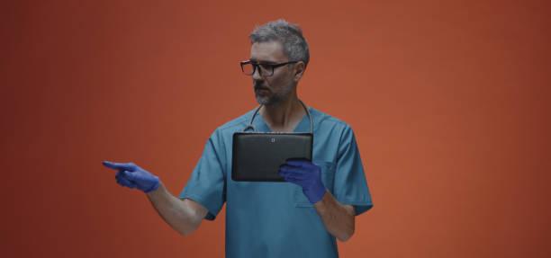 male doctor using a tablet - vr red background imagens e fotografias de stock