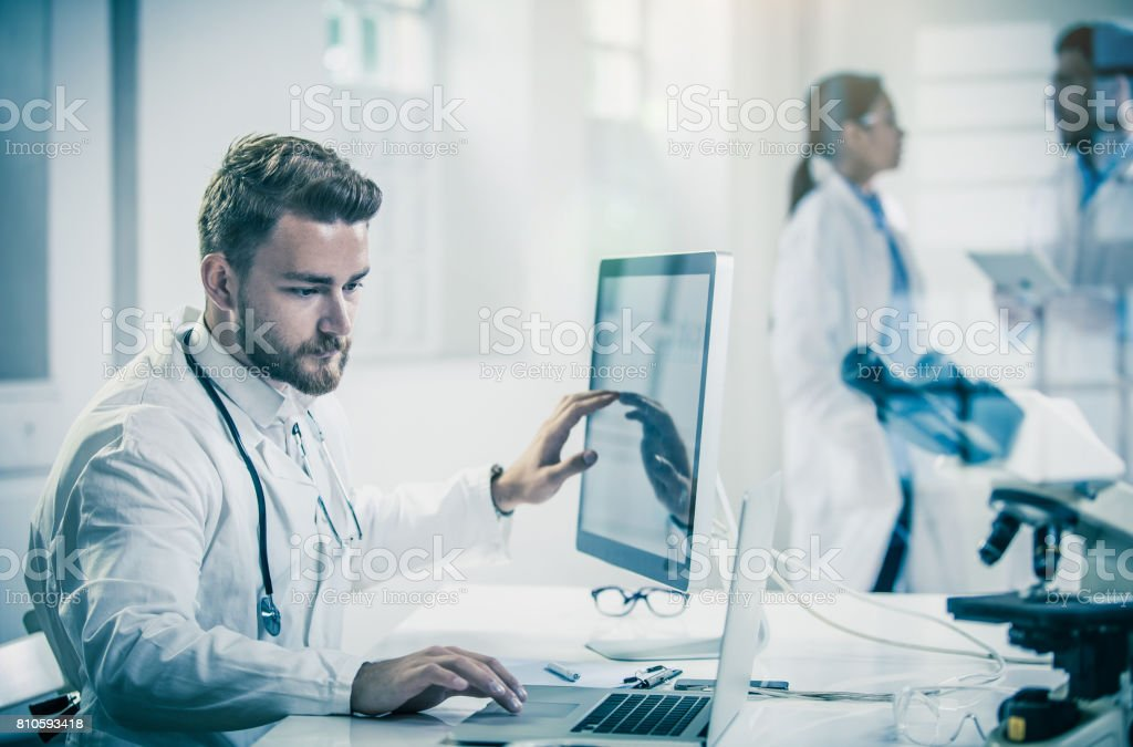 Male Doctor Using Computer With Colleagues Behind stock photo