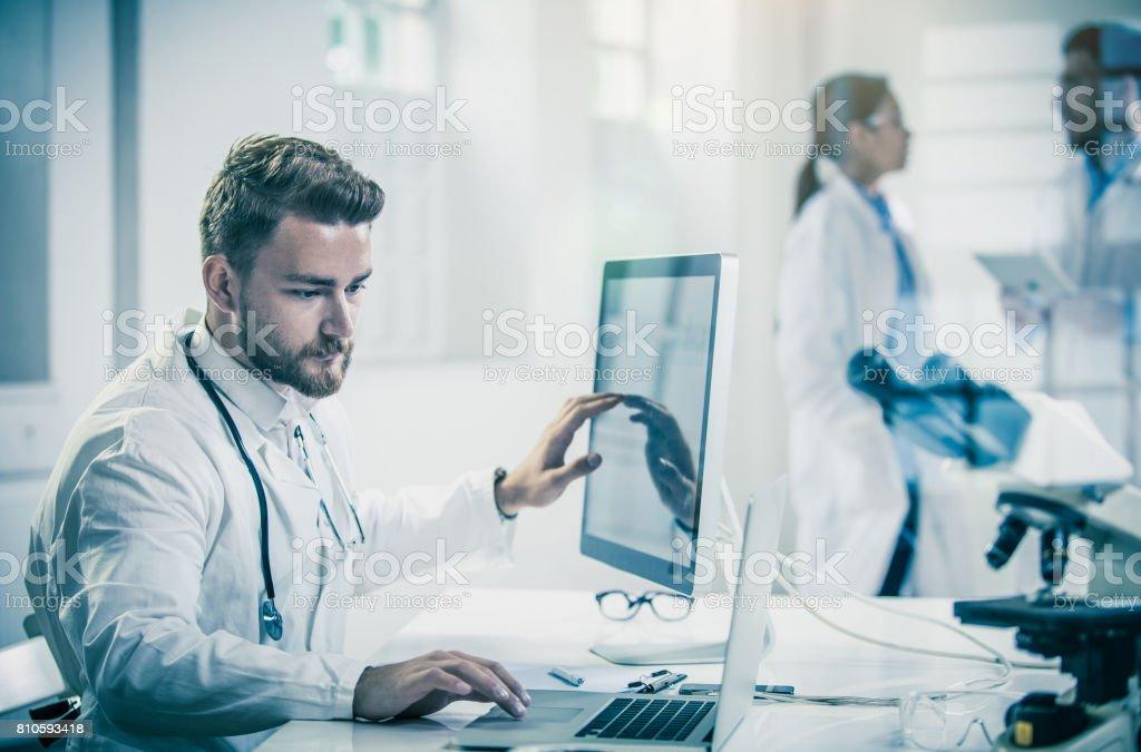 Médico de macho usando o computador com os colegas por trás - foto de acervo