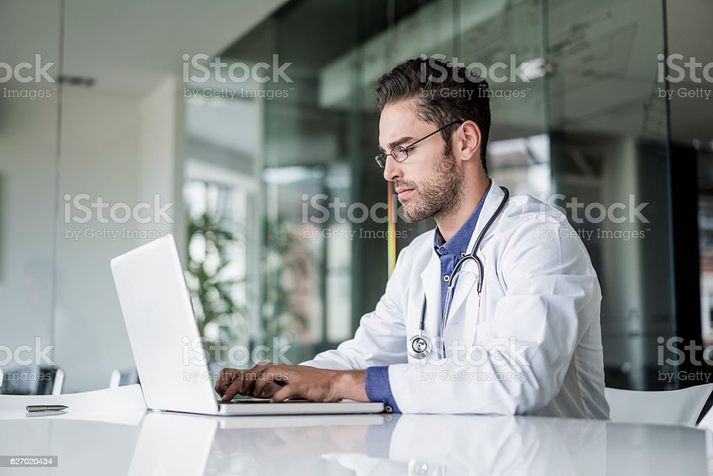 Male doctor using laptop at desk in clinic – Foto