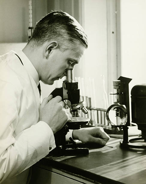 Male doctor using microscope in surgery, (B&W)  20th century stock pictures, royalty-free photos & images