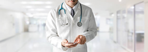 Male doctor using mobile phone at hospital. stock photo