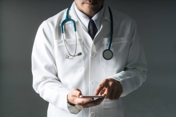 Male doctor using smartphone touching with finger stock photo
