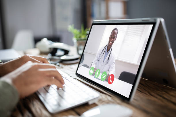 Male Doctor Video Chatting On Laptop stock photo