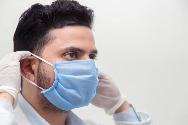 Männlicher Arzt trägt chirurgische Maske – Foto