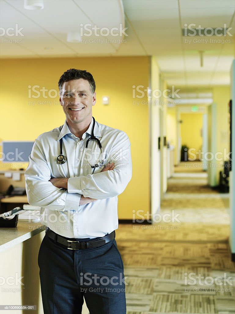 Male doctor with arms crossed, smiling, portrait royalty-free stock photo