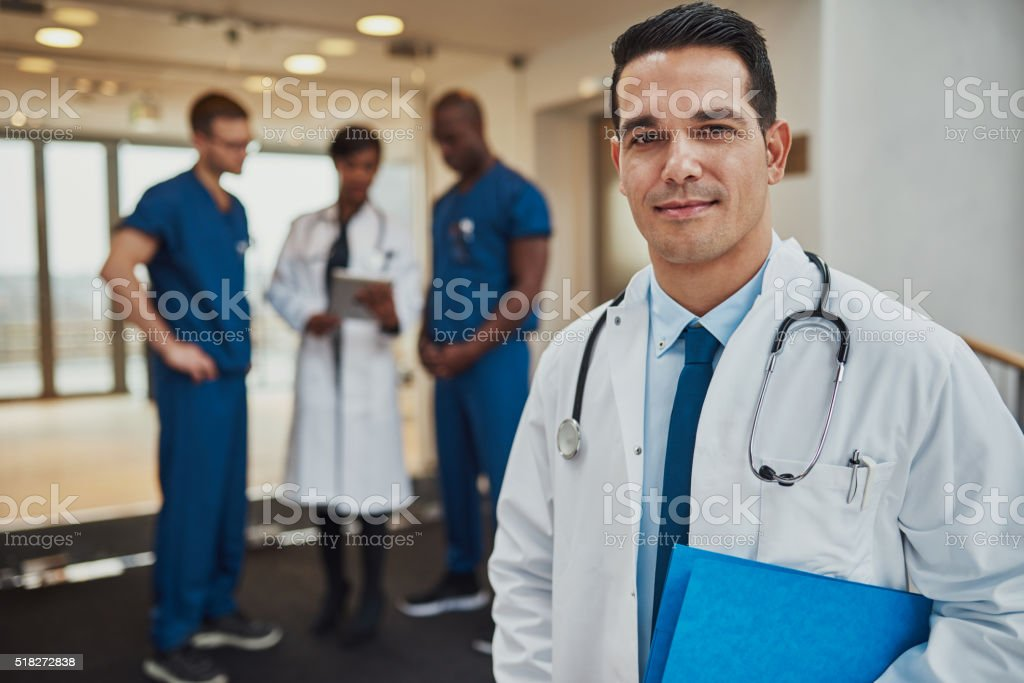Male doctor with colleagues in background stock photo