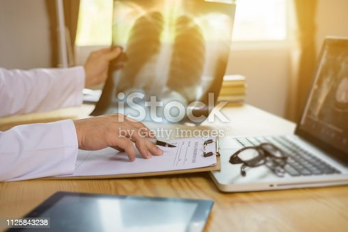 Male Doctor with files and stethoscope on hospital corridor holding clipboard and writing prescription drug order,pharmacy and  Looking at X-Ray Radiography in patient's Room,vintage color