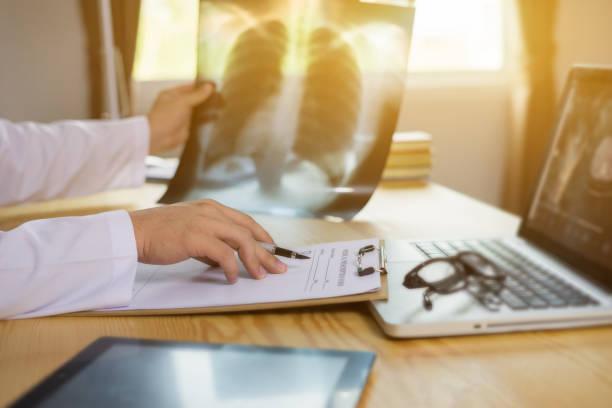 Männlichen Arzt mit Dateien und Stethoskop auf das Krankenhaus Flur Holding Zwischenablage und schreiben verschreibungspflichtiges Medikament bestellen, Apotheke und Looking at x-ray Röntgen im Patientenzimmer, Vintage Farbe – Foto