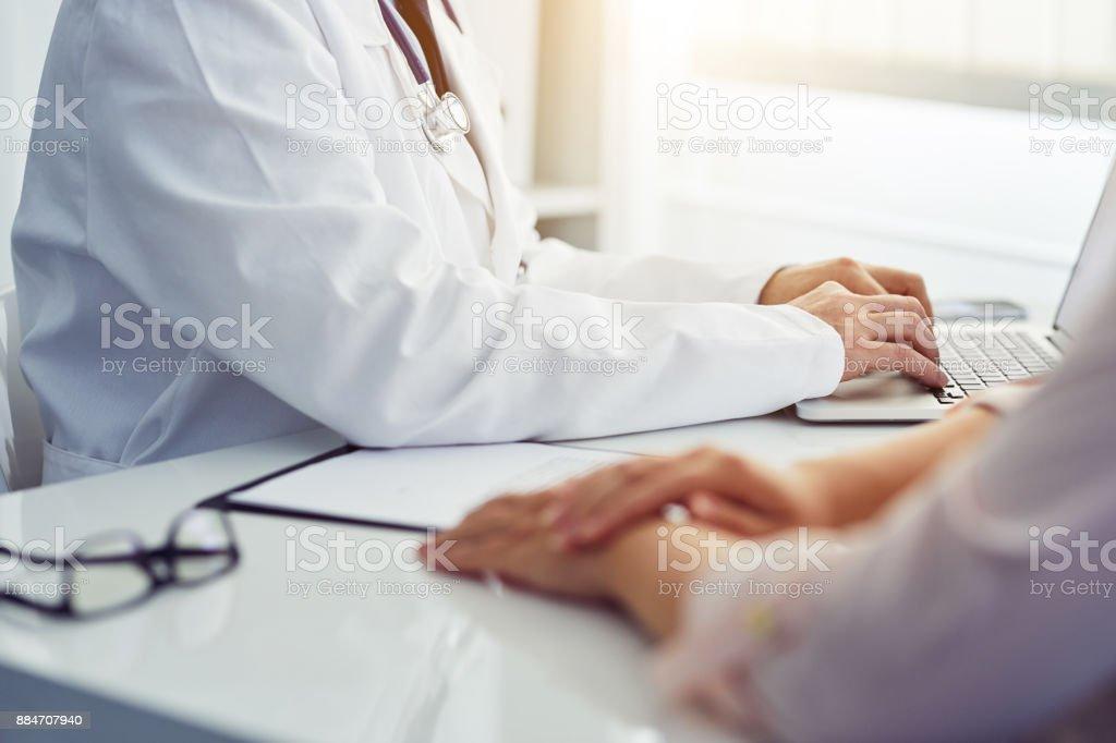 Männlichen Arzt mit dem Patienten am Schreibtisch sitzen und schreiben auf laptop – Foto