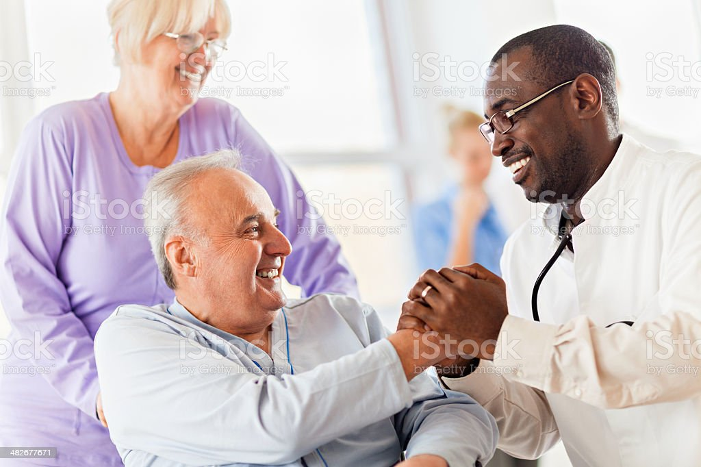 Male doctor with senior patient stock photo