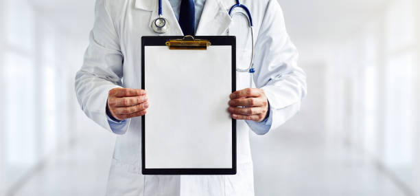Male doctor with the blank clipboard in the hospital stock photo