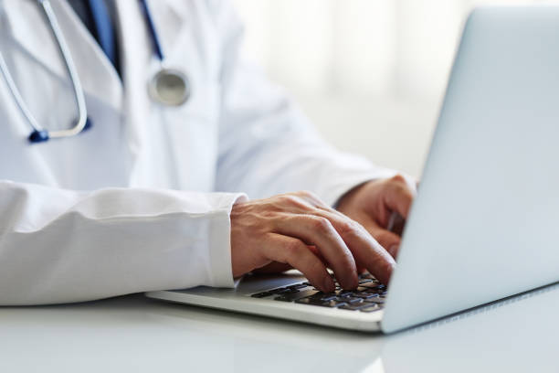 Male doctor working on laptop stock photo
