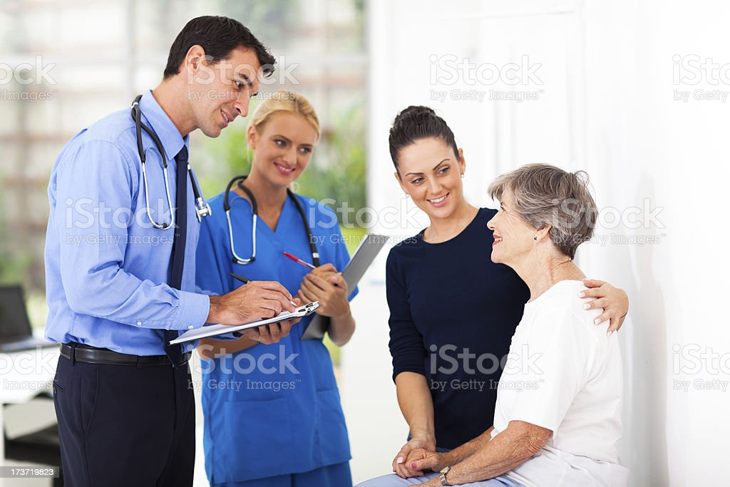 male doctor writing medical prescription for senior patient stock photo