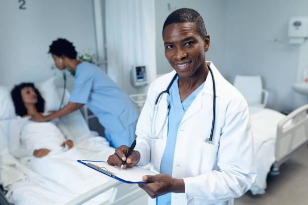 Männlicher Arzt schreibt auf Zwischenablage in der Station im Krankenhaus – Foto