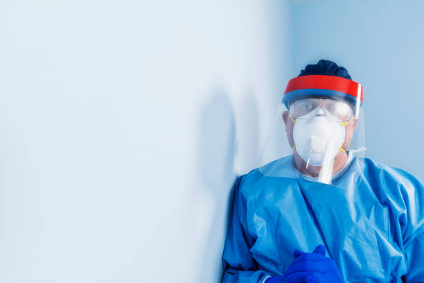 Male doctor/nurse wearing PPE leaning against a wall looking at camera with hands clasped
