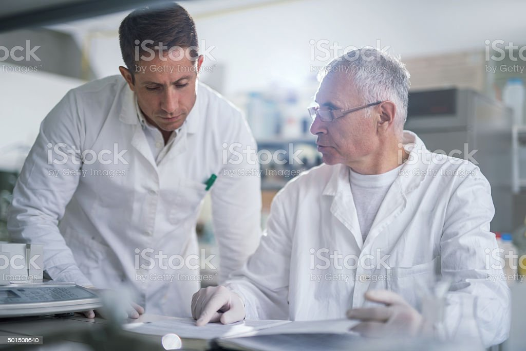 Two scientists working together in laboratory while reading medical...